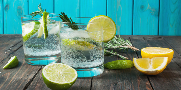Alcoholic drink gin tonic cocktail with lemon, rosemary and ice on rustic wooden table
