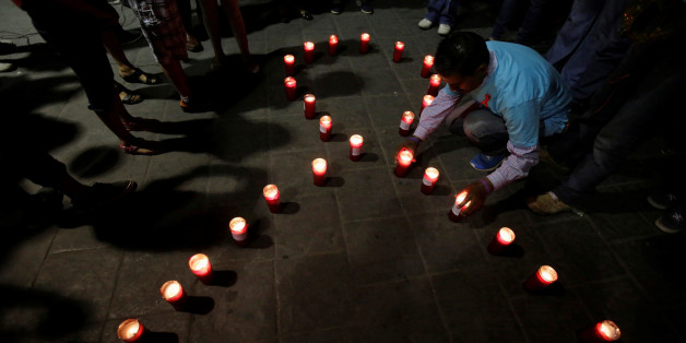 "Members of Mexico's HIV/AIDS social organizations light candles during a vigil under the slogan ""Two nations, One Heart"" to remember those killed by HIV/AIDS and deliver prevention measures to citizens over the Santa Fe international bridge, which connects Ciudad Juarez to El Paso, Texas, in Ciudad Juarez, Mexico, May 21, 2017. REUTERS/Jose Luis Gonzalez"