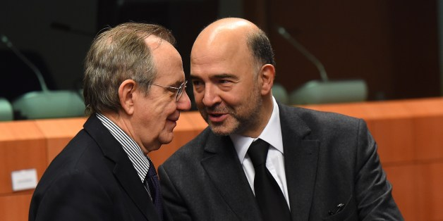 Italian Finance Minister Pier Carlo Padoan (L) and EU economic and financial affairs, taxation and customs commissioner Pierre Moscovici talk on December 8 2014 before the start of a Eurozone finance ministers meeting at EU headquarters in Brussels. AFP PHOTO / EMMANUEL DUNAND        (Photo credit should read EMMANUEL DUNAND/AFP/Getty Images)