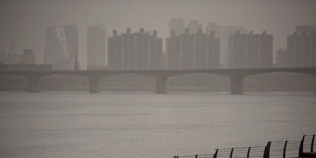 A man takes a selfie as he stands before the Han River and the Seoul city skyline during heavily polluted weather on February 23, 2015. The worst winter seasonal yellow dust in five years blanketed the Korean Peninsula, prompting the authorities to issue health warnings against the sandy, chemical-laden wind from China, according to domestic media. On a scale based on the US environmental Protection Agency standard, levels of fine particulate matter of ten micrometers or less (PM10) exceeded the