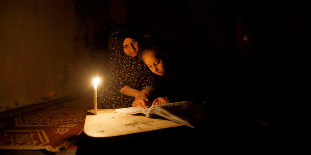 A Palestinian girl studies her lessons by a candlelight during power cut inside her family's house at Shati refugee camp in Gaza City April 25, 2017. Picture taken April 25, 2017. REUTERS/Mohammed Salem