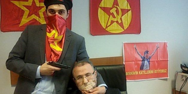 A gunman poses with Prosecutor Mehmet Selim Kiraz with a gun on his head after being taken hostage in his office in a court house in Istanbul March 31, 2015. A far-left Turkish group took the Istanbul prosecutor hostage on Tuesday and threatened to kill him, prompting special forces officers to enter the courthouse and police to evacuate the building. The Revolutionary People's Liberation Party-Front (DHKP-C) published a picture of the prosecutor with the gun to his head and said it would kill h