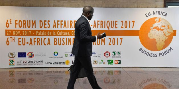A man walks past a banner at the 6th EU-Africa Business Forum on November 27, 2017, in Abidjan, ahead of the Afican Union - European Union summit. / AFP PHOTO / ISSOUF SANOGO        (Photo credit should read ISSOUF SANOGO/AFP/Getty Images)