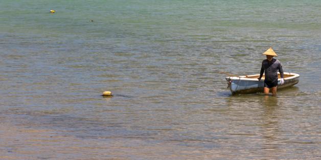 ISHIGAKI, JAPAN - AUGUST 28: Japanese fisherman in tropical lagoon with clear blue water in Kabira bay, Yaeyama Islands, Ishigaki, Japan on August 28, 2017 in Ishigaki, Japan. (Photo by Eric Lafforgue/Art In All Of Us/Corbis via Getty Images)