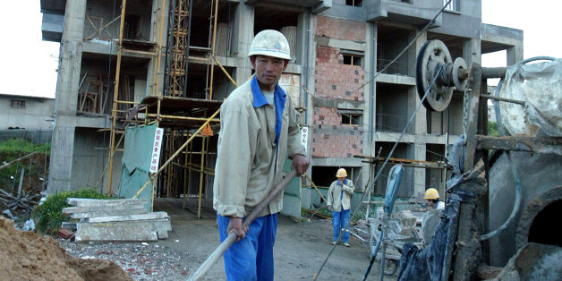 A Chinese labourer works on a construction site in Algiers, March 31, 2004. The Algerian national Agency of Improvement and Development (AADL) has contracted with a Chinese construction company to build some 40,000 appartments within a record delivery time. According to the contract, at least half the appartment buildings must be ready to be inhabited by the end of April 2004. REUTERS/Louafi Larbi  LL/MAL/THI