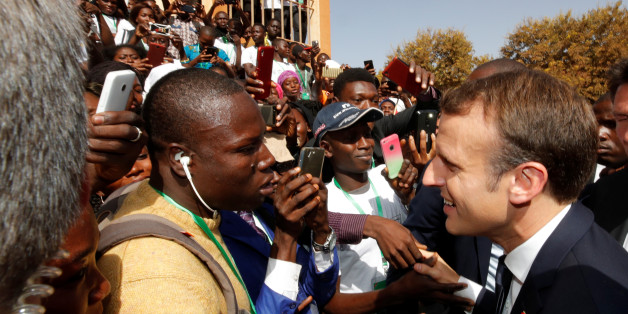 French President Emmanuel Macron shakes hands with people in the crowd as he leaves the Ouagadougou University, in Ouagadougou, Burkina Faso, November 28, 2017. REUTERS/Philippe Wojazer