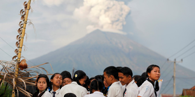 School children ride on the back of a truck on their way to school as Mount Agung volcano erupts in the background near Amed, Karangasem Regency, Bali, Indonesia November 28, 2017. REUTERS/Nyimas Laula
