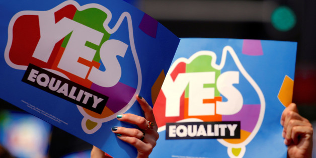 People participating in a march hold aloft posters supporting a 'Yes' vote in a non-binding poll, conducted by post, to inform the government on whether voters want Australia to become the 25th nation to permit same-sex marriage, in central Sydney, Australia, October 21, 2017. Picture taken October 21, 2017.      REUTERS/David Gray