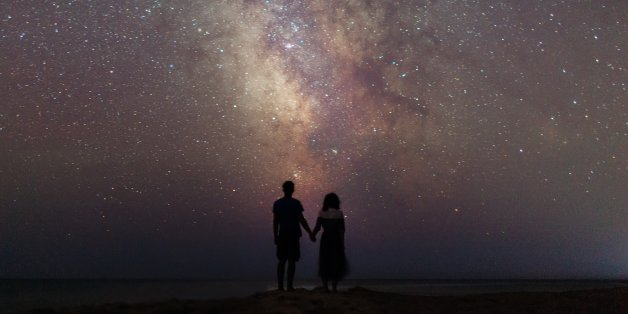 Young Caucasian couple walking near the sea  at night under the starry sky