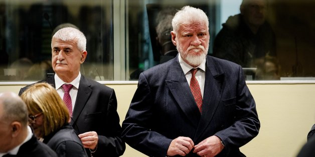 Former Bosnian Croat Defense Minister Bruno Stojic and former Croatian general Slobodan Praljak (R) are pictured prior to the judgement in their appeals case, along with four other former Bosnian Croat political and military leaders, on November 29, 2017 at the Hague international court, in the court's final verdict for war crimes committed during the break-up of Yugoslavia.  / AFP PHOTO / ANP AND POOL / Robin van Lonkhuijsen        (Photo credit should read ROBIN VAN LONKHUIJSEN/AFP/Getty Images)