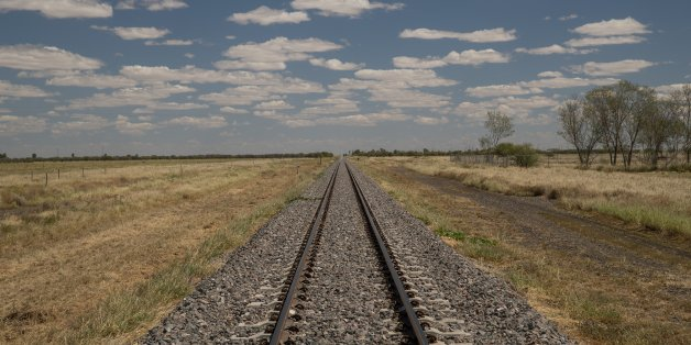 A railway line in the Queensland outback with a blue sky with clouds
