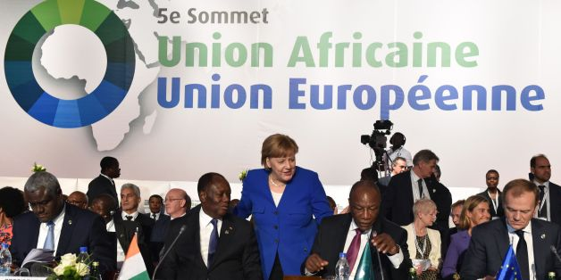 German Chancellor Angela Merkel (C) arrives to greet Ivory Coast's President Alassane Ouattara (2L) and Guinea's President and African Union (AU) chairman Alpha Conde (2R) next to African Union (AU) Commission chairman Moussa Faki (L) and European Council President Donald Tusk during the 5th African Union - European Union (AU-EU) summit in Abidjan, on November 29, 2017.Ivory Coast President opened a Europe-Africa summit on November 29, calling for 'all urgent measures' to end migrant abuses, inc