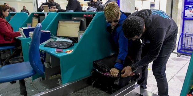 A Tunisian couple bound for London pack away their electronics in their luggage as they check-in for a flight at Tunis-Carthage International Airport on March 25, 2017.The United States this week announced a ban on all electronics larger than a standard smartphone on board direct flights out of eight countries across the Middle East, in effect from March 25, 2017. US officials would not specify how long the ban will last, but Emirates told AFP that it had been instructed to enforce the measures
