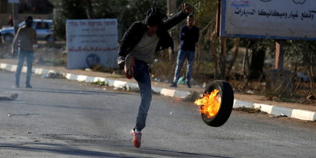A Palestinian protester kicks a burning tire during clashes with Israeli troops near the West Bank city of Nablus, November 30, 2017. REUTERS/Mohamad Torokman