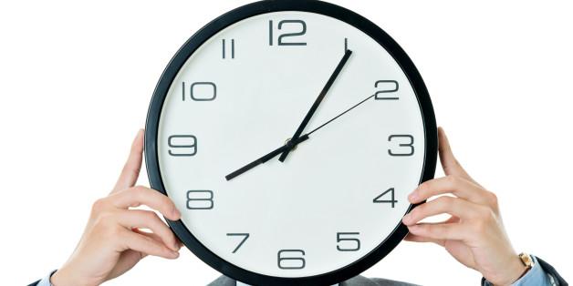 Businessman holding clock against white background.