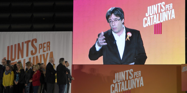 'Junts per Catalonia' (All for Catalonia) grouping cadidate for the upcoming Catalan regional election, Carles Puigdemont, appears on a screen to take part in the campaign opening meeting in Barcelona, on December 4, 2017.Catalans remain deeply split on independence, and several polls suggest pro-secession parties might struggle to win enough seats to form a new regional government after the December 21 regional election. / AFP PHOTO / LLUIS GENE        (Photo credit should read LLUIS GENE/AFP/G
