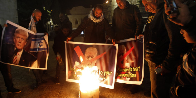 Palestinian protesters burn pictures of US President Donald Trump at the manger square in Bethlehem on December 5, 2017.   US President Donald Trump told Palestinian leader Mahmud Abbas in a phone call that he intends to move the US embassy from Tel Aviv to Jerusalem, Abbas's office said. / AFP PHOTO / Musa AL SHAER        (Photo credit should read MUSA AL SHAER/AFP/Getty Images)
