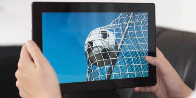 Concept of streaming live sports events. Soccer ball hits the net on a digital tablet.