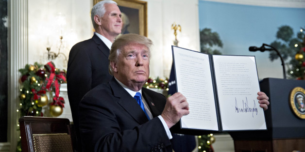 U.S. President Donald Trump holds up a proclamation next to U.S. Vice President Mike Pence, left, after making a statement on Jerusalem in the Diplomatic Room of the White House in Washington, D.C., U.S., on Wednesday, Dec. 6, 2017. Trump formally declared Jerusalem to be Israel's capital and is directing the State Department to start the process of moving the U.S. embassy there from Tel Aviv, a historic shift of U.S. policy that could inflame key allies. Photographer: Andrew Harrer/Bloomberg vi