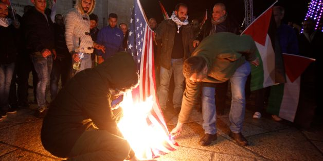Palestinian demonstrators burn the US flag in Bethlehem's Manger Square in protest to the declaration of the US president declaring Jerusalem as Israel's capital on December 6, 2017.Abbas said the United States can no longer play the role of peace broker after Donald Trump's decision on Wednesday to recognise Jerusalem as Israel's capital. / AFP PHOTO / Musa AL SHAER        (Photo credit should read MUSA AL SHAER/AFP/Getty Images)