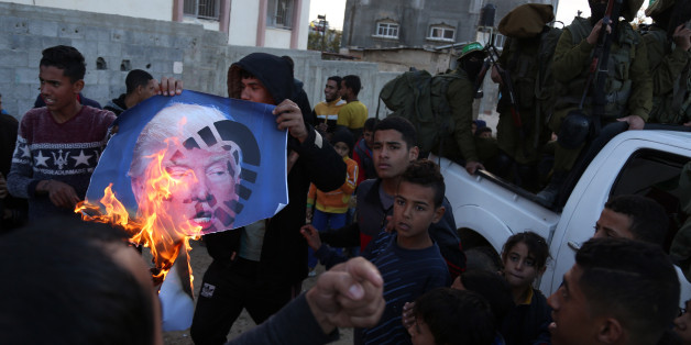 Palestinians burn posters of Israeli Prime Minister Benjamin Netanyahu and U.S. President Donald Trump, during a protest against the U.S. decision to recognize Jerusalem as Israel's capital, in Gaza City Thursday, Dec. 7, 2017. (Photo by Majdi Fathi/NurPhoto via Getty Images)