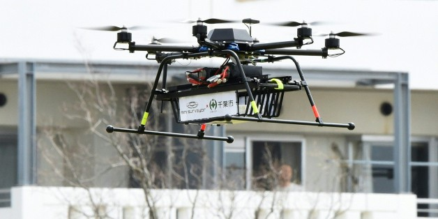 A drone developed by Japan's Autonomous Control Systems Laboratory (ACSL) flies beside a condomimium for a field test in Chiba, suburb of Tokyo, on April 11, 2016. The Japanese government, Chiba City and ACSL jointly carried out a proof experiment for a door-to-door parcel delivery service by the drone equipped with a GPS function. / AFP / TORU YAMANAKA        (Photo credit should read TORU YAMANAKA/AFP/Getty Images)