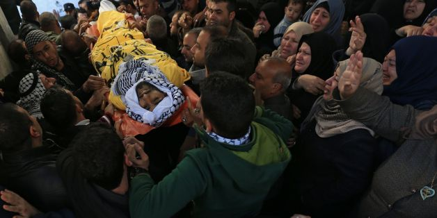 Palestinian mourners carry the body of Mahmoud al-Masri, a 30-year-old Palestinian man who was killed the previous day in clashes with Israeli troops, during his funeral in Khan Younis, in the southern Gaza Strip, on December 9, 2017.Clashes, Palestinian rocket fire and Israeli air strikes killed at least two people and wounded dozens of others on December 8 in violence linked to US President Donald Trump's declaration of Jerusalem as Israel's capital. / AFP PHOTO / MOHAMMED ABED        (Photo c