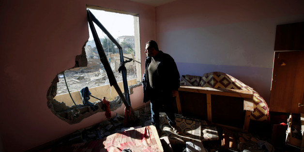 A Palestinian man looks out of his apartment that was damaged in an Israeli airstrike at a nearby militant target in the northern Gaza Strip December 9, 2017. REUTERS/Mohammed Salem