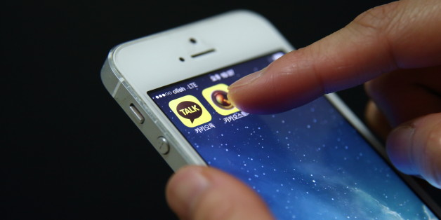 The app icon for KakaoTalk, a messaging app developed by Kakao Corp., left, is displayed on an Apple Inc. iPhone 5 in this arranged photograph taken in Seoul, South Korea, on Monday, Dec. 30, 2013. Kakao is South Korea's biggest mobile messenger operator. Photographer: SeongJoon Cho/Bloomberg via Getty Images