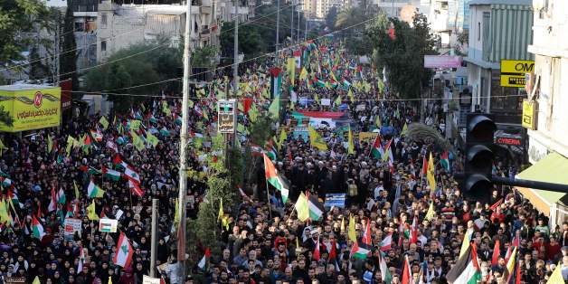 Supporters of Lebanon's Hezbollah Shiite movement wave national, Palestinian and Hezbollah flags during a massive rally in the Lebanese capital Beirut on December 11, 2017 in protest against the US president's controversial recognition of Jerusalem as Israel's capital. / AFP PHOTO / Joseph EID        (Photo credit should read JOSEPH EID/AFP/Getty Images)