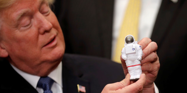 U.S. President Donald Trump holds a space astronaut toy as he participates in a signing ceremony for Space Policy Directive at the White House in Washington D.C., U.S., December 11, 2017. REUTERS/Carlos Barria     TPX IMAGES OF THE DAY