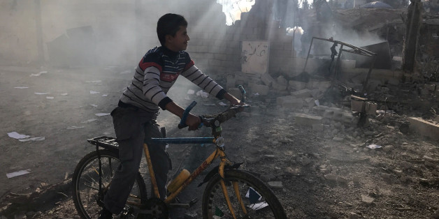 A Palestinian boy rides a bicycle near a militant target that was hit in an Israeli airstrike in the northern Gaza Strip. REUTERS/Mohammed Salem
