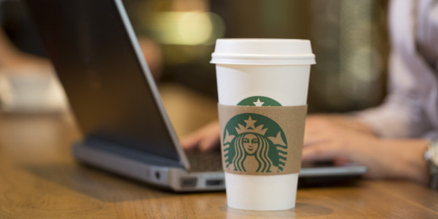 The Starbucks Corp. logo sits on a carboard coffee cup as a customer uses a laptop computer inside a Starbucks Corp. coffee shop in London, U.K., on Monday, June 9, 2014. U.K. services companies' confidence rose to a record this quarter, indicating continued expansion in the largest part of the economy, the Confederation of British Industry said. Photographer: Jason Alden/Bloomberg via Getty Images