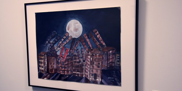 A painting by detainee Ahmed Robbani is viewed on November 22, 2017, part of an exhibit from Guantanamo Bay, Cuba at John Jay College of Criminal Justice in New York.The art is striking -- a miniature three-masted ship in cardboard, with bits of T-shirt for the sails and threads from a prayer cap for ropes. A picture of a huge mosque at water's edge. A shadowy and faceless Statue of Liberty.The pieces are all part of a surprising exhibit in New York with an unlikely source -- the US military pri