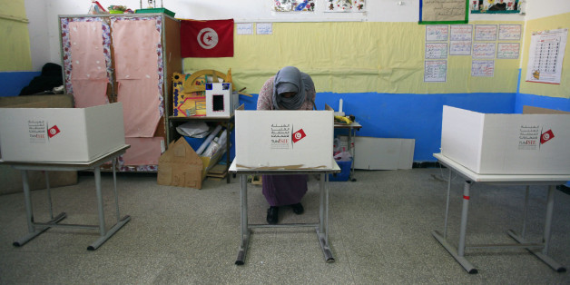 A Tunisian woman casts her ballot in the capital Tunis December 21, 2014. Tunisians began voting on Sunday in a presidential run-off election that completes the country's last steps to full democracy nearly fours years after an uprising that toppled autocrat Zine El-Abidine Ben Ali. REUTERS/Anis Mili (TUNISIA - Tags: ELECTIONS POLITICS)