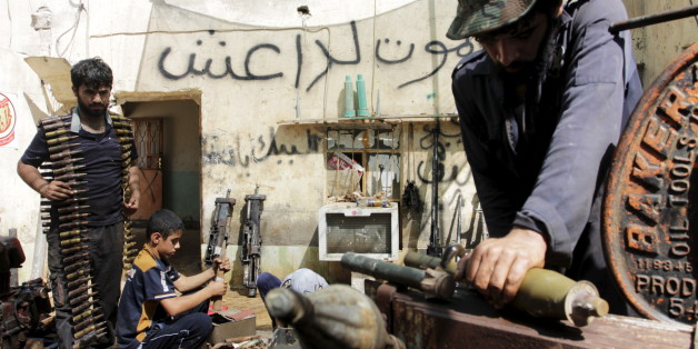"Iraqi volunteers fix the weapons of the Hashid Shaabi militia, at a shop on the outskirts of Basra June 16, 2015. The Arabic writing on the wall reads, ""Death to DAESH (Arabic name for the Islamic State, or ISIL)"". REUTERS/Stringer"