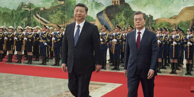 BEIJING, CHINA - DECEMBER 14: South Korean President Moon Jae-In (R) and Chinese President Xi Jinping (L)  review the Chinese honour guard during a welcome ceremony at the Great Hall of the People on December 14, 2017 in Beijing, China. (Photo by Nicolas Asfouri-Pool/Getty Images)