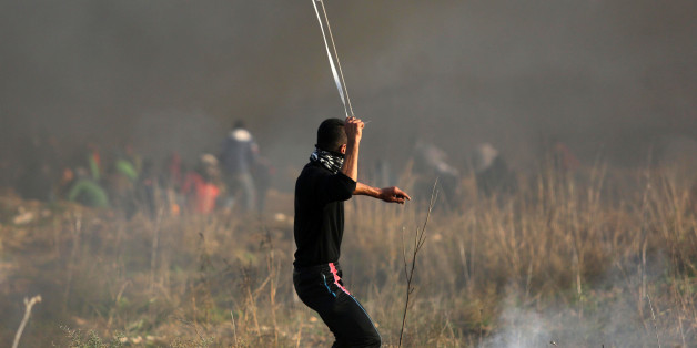 Palestinian protesters hurl stones towards Israeli troops during clashes following a protest against US President Donald Trump's decision to recognize Jerusalem as the capital of Israel, near the Gaza-Israel borders, East of Gaza City, 15 December 2017. (Photo by Majdi Fathi/NurPhoto via Getty Images)