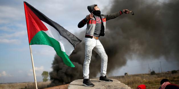 Un manifestant palestinien lance une pierre contre les troupes israéliennes pendant une manifestation contre la décision de Donald Trump de reconnaître Jérusalem comme la capitale d'Israël, à l'est de Gaza, 15 décembre 2017.
