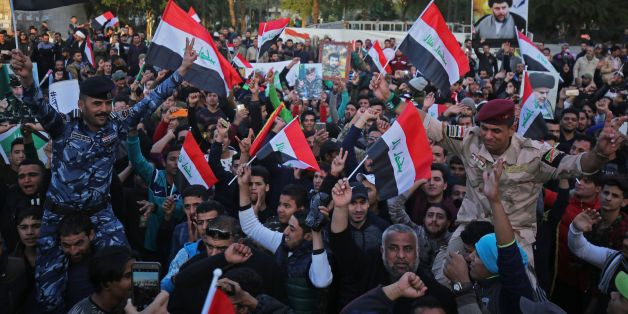 Iraqis wave their national flag in Baghdad's Tahrir Square on December 10, 2017, during a gathering celebrating the end of the three-year war against the Islamic State (IS) group.Baghdad declared victory in its war to expel the jihadists, three years after the group proclaimed a cross-border 'caliphate' stretching into Syria, endangering Iraq's very existence. / AFP PHOTO / AHMAD AL-RUBAYE        (Photo credit should read AHMAD AL-RUBAYE/AFP/Getty Images)