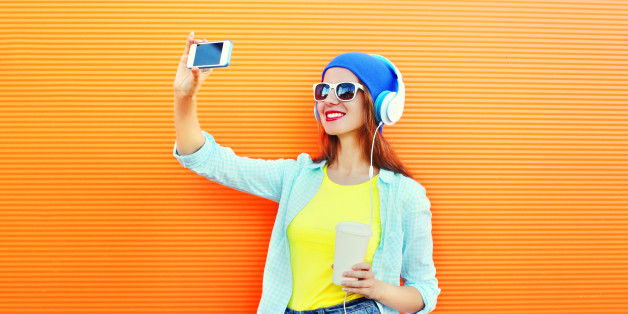 Fashion pretty cool girl makes self portrait on smartphone over colorful orange background