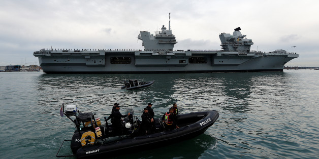Police officers stand guard in a rigid inflatable boat (RIB) as the Royal Navy's new aircraft carrier HMS Queen Elizabeth arrives in Portsmouth, Britain August 16, 2017. REUTERS/Peter Nicholls