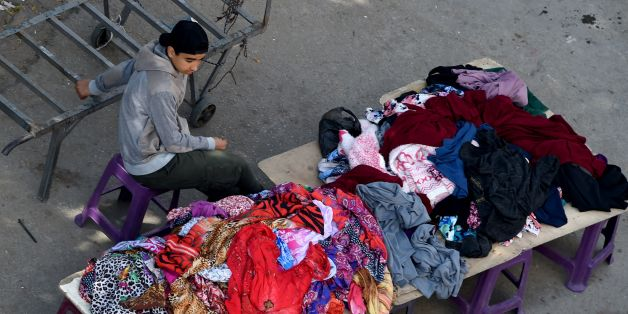 A Tunisian boy sells clothes at a market in the centre of Tunis on April 14, 2017.