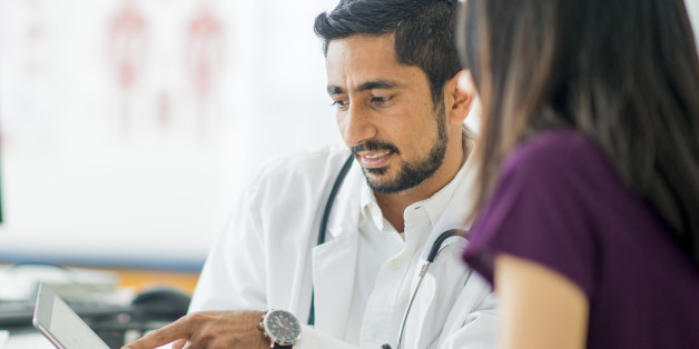 A doctor is talking to a patient about her condition at her appointment.