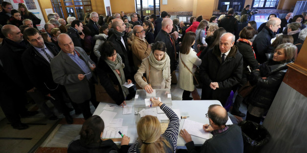 A woman casts her ballot as others wait to vote in Catalonia's regional elections at a polling station in Barcelona, Spain December 21, 2017. REUTERS/Albert Gea