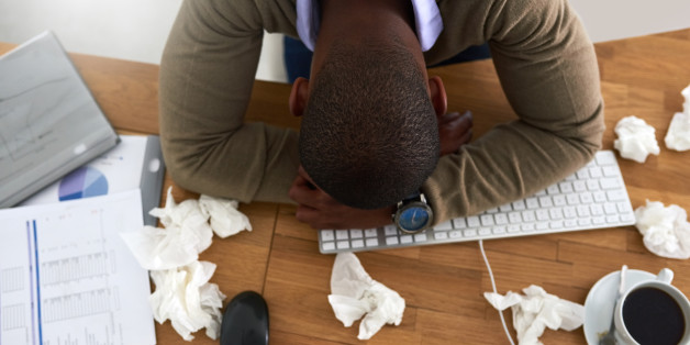 High angle shot of a young businessman feeling ill at his work desk