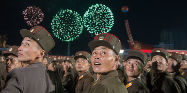 TOPSHOT - In a photo taken on September 6, 2017, Korean People's Army (KPA) soldiers cheer while watching fireworks during a mass celebration in Pyongyang for scientists involved in carrying out North Korea's largest nuclear blast to date.Citizens of the capital lined the streets September 6 to wave pink and purple pom-poms and cheer a convoy of buses carrying the specialists into the city, and toss confetti over them as they walked into Kim Il-Sung Square. / AFP PHOTO / Kim Won-Jin        (Phot