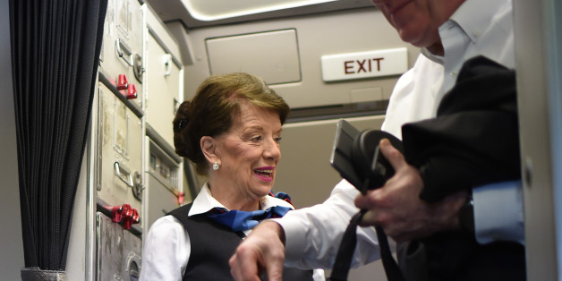 American Airlines longest serving flight attendant, Bette Nash (L), 81 years old, greets passengers disembarking from her daily return flight to Boston at Ronald Reagan Washington Airport in Arlington, Virginia on December 19, 2017.  American Airlines Flight 2160 from Boston has just arrived in Washington, D.C., and Bette Nash, 81, helps the passengers disembark. After six decades crossing the skies as a flight attendant, Nash still has impeccable style, incredible energy and a constant smile. I