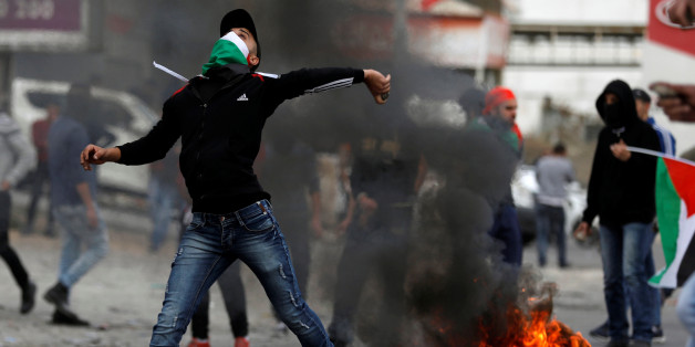 "A Palestinian demonstrator hurls a stones towards Israeli troops during clashes at a protest as Palestinians call for a ""Day of Rage"" in response to U.S. President Donald Trump's recognition of Jerusalem as Israel's capital, near the West Bank city of Nablus December 22, 2017. REUTERS/Mohamad Torokman"