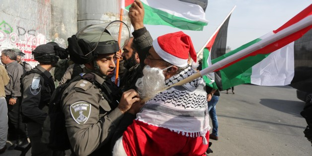 BETHLEHEM, WEST BANK - DECEMBER 23 :  Israeli security forces intervene protesters dressed up as Santa-Claus during a protest against U.S. President Donald Trumps announcement to recognize Jerusalem as the capital of Israel and plans to relocate the U.S. Embassy from Tel Aviv to Jerusalem, in Bethlehem, West Bank on December 23, 2017. (Photo by Issam Rimawi /Anadolu Agency/Getty Images)